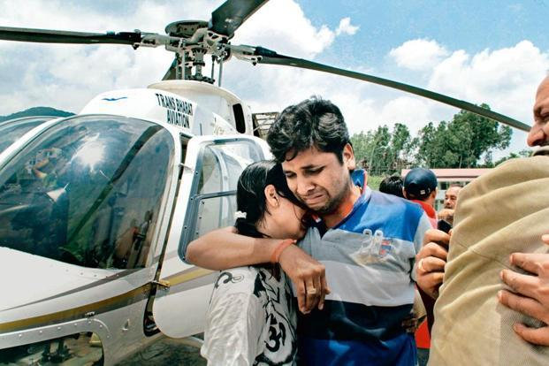 A couple console each other after being evacuated from Uttarakhand. Photo: AP